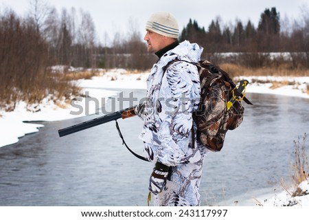 hunter with gun on the river bank