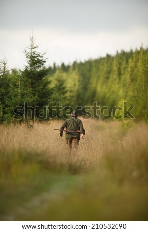 hunter with his rifle in spring forest, hunter holding a rifle and  waiting for prey, hunter shooting, gamekeeper on the walk - stock photo