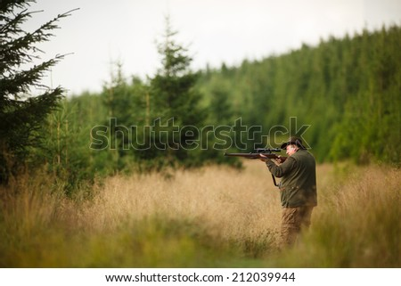 hunter with his rifle in spring forest, hunter holding a rifle and waiting for prey, hunter shooting, on the walk in forest - stock photo