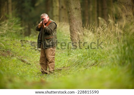 hunter with his rifle in spring forest, hunter holding a rifle and waiting for prey, hunter aiming and shooting - stock photo