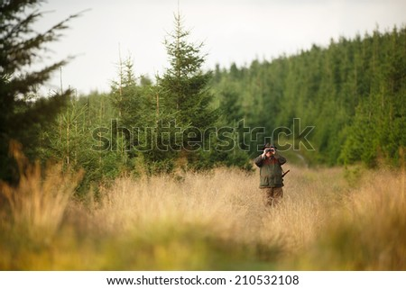 hunter with his rifle in spring forest, hunter holding binoculars and  waiting for prey, hunter aiming with telescope - stock photo