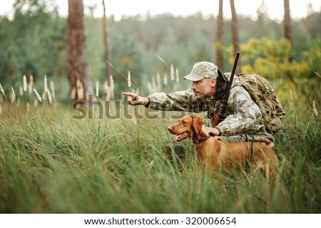 Hunter with Rifle and Dog in forest - stock photo