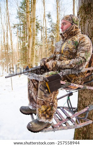 Hunter with rifle in a tree stand - stock photo
