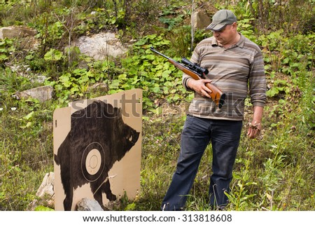 hunter with rifle near the target - stock photo