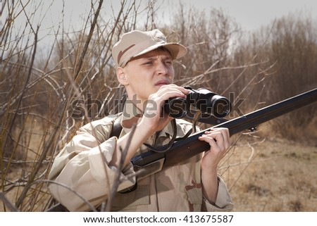 Hunter with shotgun looking through binoculars in forest