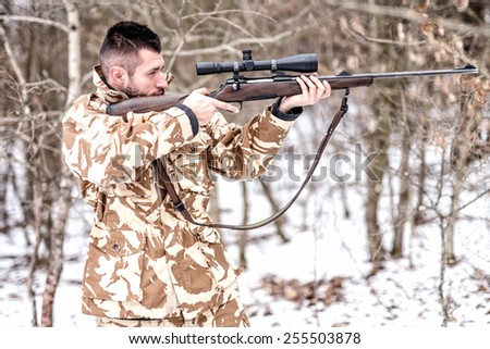 Hunter with sniper aiming and shooting in the forest during winter hunting season - stock photo