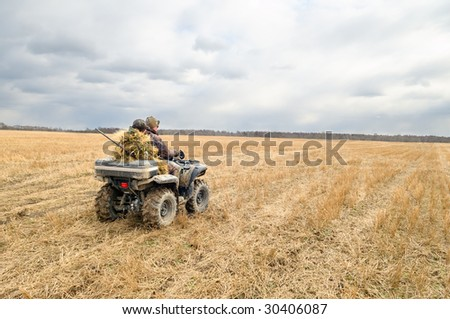 Hunters on quad bikes.