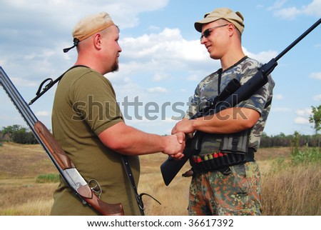hunters shakes hands mutually - stock photo