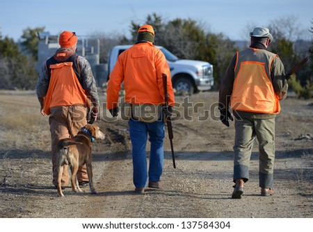 hunters with a guide in the field - stock photo