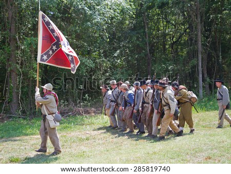 HUNTERSVILLE, NC - JUNE 6, 2015:  Reenactors in Confederate uniforms march under their battle flag during an American Civil War reenactment at Historic Latta Plantation. - stock photo
