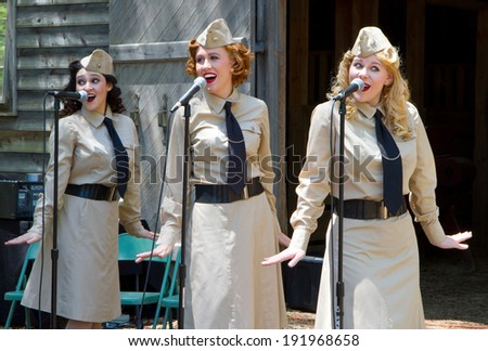 HUNTERSVILLE, NC - MAY 3, 2014:  Three female American singers performing at Historic Latta Plantation as part of a World War II reenactment in commemoration of the 70th anniversary of D-Day. - stock photo