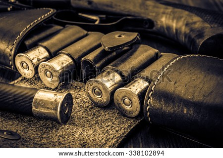 Hunting ammunition 12 gauge in leather bandolier and shotgun on a wooden table. Focus on the cartridges, image vignetting and the yellow toning - stock photo