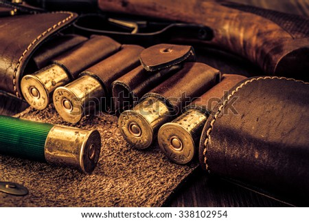 Hunting ammunition 12 gauge in leather bandolier and shotgun on a wooden table. Focus on the cartridges, image vignetting and the yellow-blue toning - stock photo