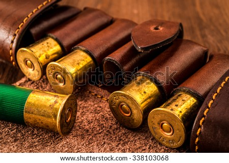 Hunting ammunition 12 gauge in leather bandolier on a wooden table. Focus on the cartridges - stock photo