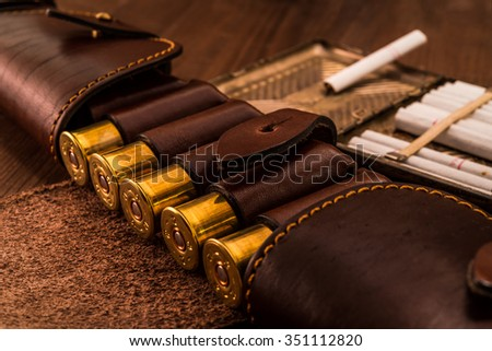 Hunting ammunition 12 gauge in leather bandolier with cigarette case and cigarettes on a wooden table. Focus on the cartridges - stock photo