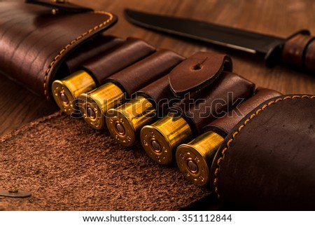 Hunting ammunition 12 gauge in leather bandolier with combat knife on a wooden table. Focus on the cartridges - stock photo