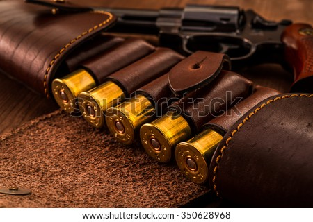 Hunting ammunition 12 gauge in leather bandolier with revolver on a wooden table. Focus on the cartridges - stock photo