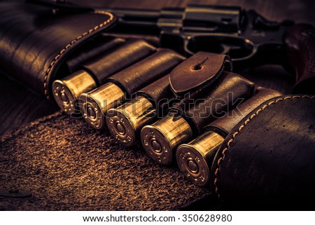 Hunting ammunition 12 gauge in leather bandolier with revolver on a wooden table. Focus on the cartridges, image vignetting and the yellow-blue toning - stock photo