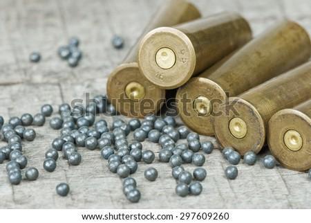 Hunting cartridges and lead shot  on the background of old wooden boards