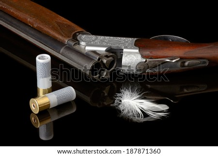 hunting gun with white feather and cartridge. - stock photo