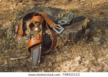 Hunting knife in leather sheath, belt and army compass. Still life with hunting equipment in the woods