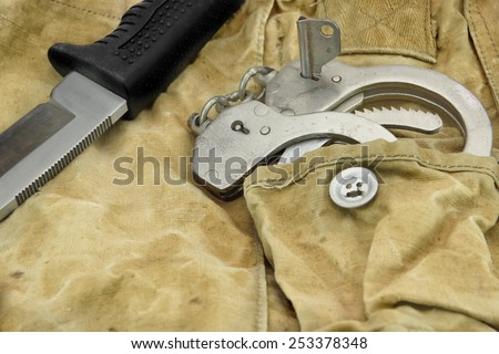 Hunting Knife with Rubberized  Handle and  Handcuffs on the Camouflage Baggy Background - stock photo