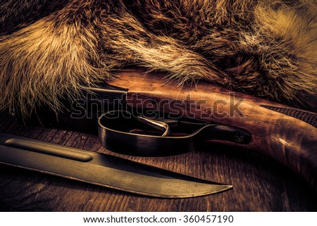 Hunting rifle with combat knife lying next to the animal's fur produced. View close-up, image vignetting and the yellow-blue toning - stock photo