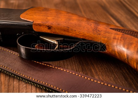 Hunting rifle with leather belt lying on a wooden table