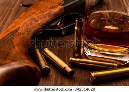 Hunting rifle with the casings from bullets and glass of whiskey close-up. Focus on the trigger of the rifle - stock photo