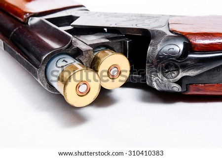 Hunting shotgun and ammunition on white background. Cartridges for hunting gun. Close up view showing mechanism of hunting rifle. Isolated on white.