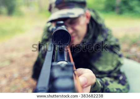 hunting, war, army and people concept - close up of young soldier, ranger or hunter with gun in forest - stock photo