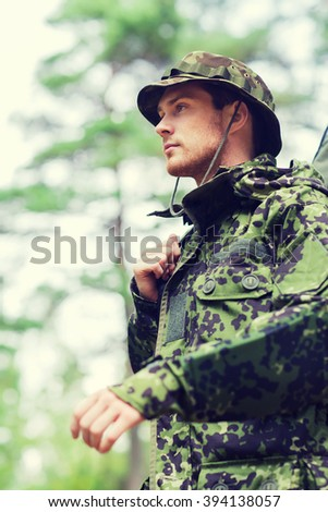 hunting, war, army and people concept - young soldier, ranger or hunter with gun walking in forest