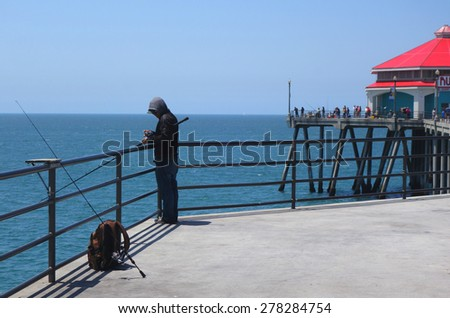 Young man fishing off a pier stock images royalty free for Huntington beach pier fishing
