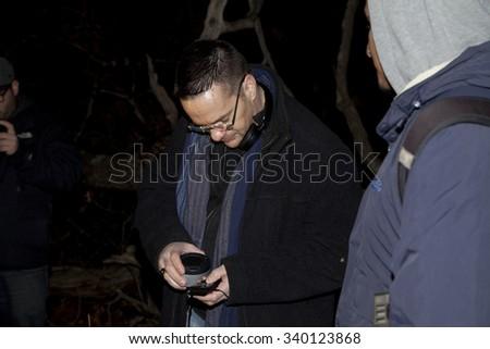 HUNTINGTON, NEW YORK, USA - NOVEMBER 14: Ron Yacovetti checks recording device  as the Brooklyn Paranormal Society of NY investigates Mount Misery Road in Long Island.  Taken November 14, 2015 in NY. - stock photo