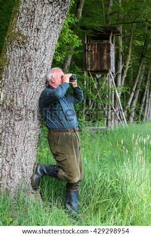 Huntsman leaning on tree in front of the pulpit, and observed the area through his binoculars