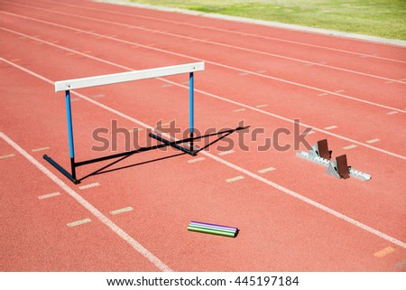 Hurdle, relay baton and a starting block kept on a running track in stadium - stock photo