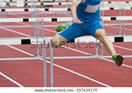 hurdle runner leaping over the hurdles - stock photo