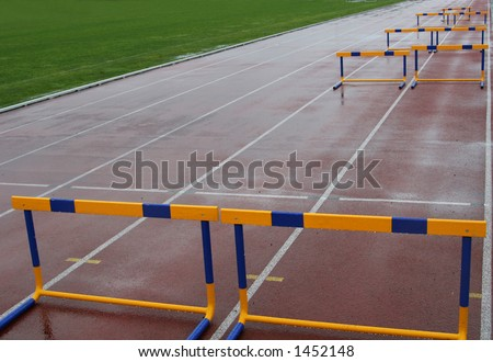 hurdles on a wet track field after heavy rain, with green wet grass showing on the left side - stock photo