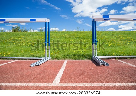 Hurdles stacked at the edge of athletics race track on a sunny summer day, green grass and blue sky in the background - stock photo