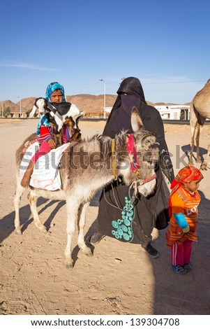 HURGHADA, EGYPT - APR 10: Unidentified arabic family with goat and donkey on the local bus station near Hurghada on 10 Apr 2013. This bus station is tourist attraction on the way to Luxor.