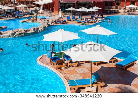 HURGHADA, EGYPT - CIRCA NOV, 2015: Swimming pool with sun parasols is in the Egyptian hotel. The Alf Leila Wa Leila spa (1001 Nights) is one of the Pickalbatros  - stock photo