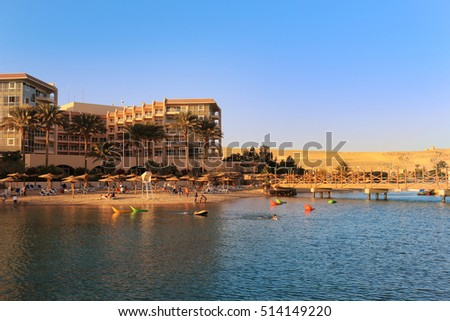 Hurghada, Egypt - Feb 7, 2016: People enjoying the beach area with sun shades and lounging chairs at a resort on the Red Sea in Hurghada, Egypt