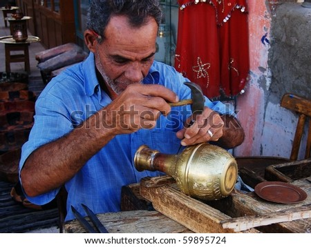 HURGHADA, EGYPT - OCTOBER 18: Uknown forger produces gold vase on October 18, 2008 in Bazaar, Hurghada, Egypt. - stock photo