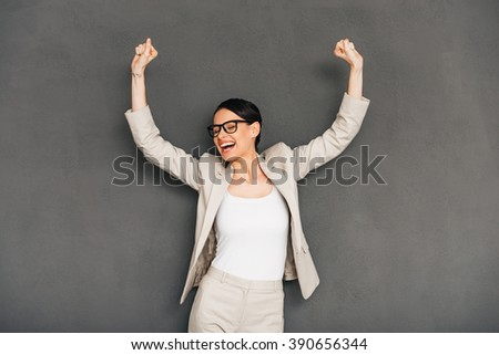 Hurray! Cheerful young businesswoman in glasses gesturing and keeping her mouth open while standing against grey background - stock photo