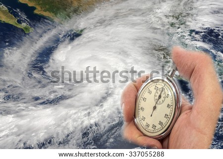 Hurricane Patricia and Hand Holding old Stopwatch. Concept of Climate change. Elements of this image furnished by NASA - stock photo