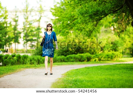 Hurrying woman walking fast trough park on a date - stock photo