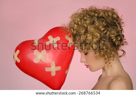 hurt woman with ball in shape of heart on pink background - stock photo