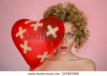 hurt young woman with ball in shape of heart on pink background - stock photo