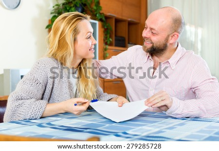 Husband and long-haired wife reading insurance contract and smiling