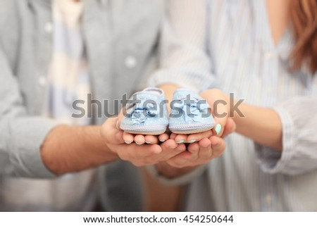 Husband and pregnant woman holding baby shoes, closeup - stock photo